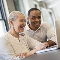 2 coworkers in office smiling at laptop
