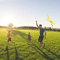 father and children flying kite at park