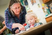Resident works on art project with toddler