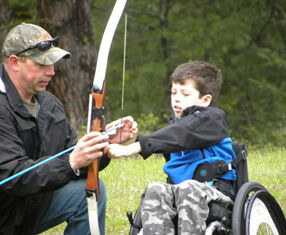 Boy in wheelchair holding bow and arrow