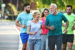 Senior couple running with group