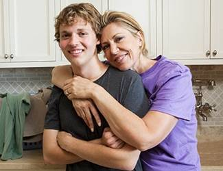 Teenage son and mother embracing in kitchen