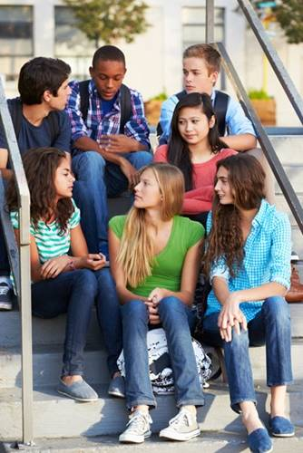 Group of diverse teenagers sitting on steps and talking