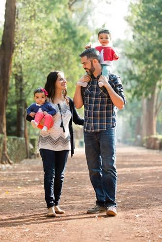 Latino family walking outdoors with young children