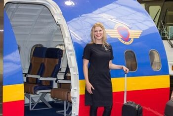 flight attendant in front of airplane simulation
