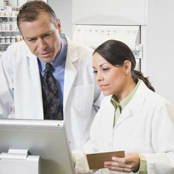 Two pharmacists consulting computer