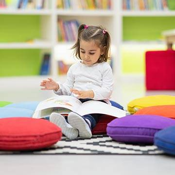 Toddler seated among pillows reading a book