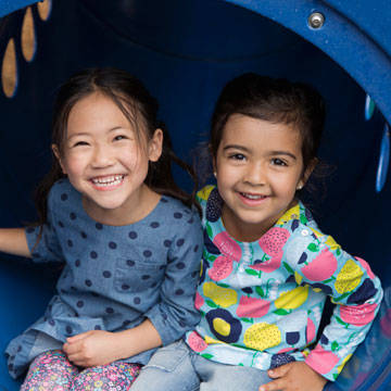 Two young girls sitting in a tube slide