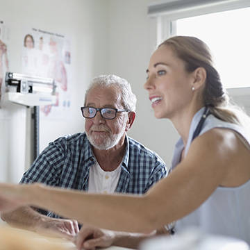 Medical clinician helping patient login to their account