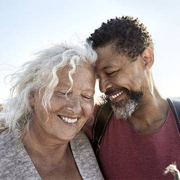 Mature woman and man embracing on beach