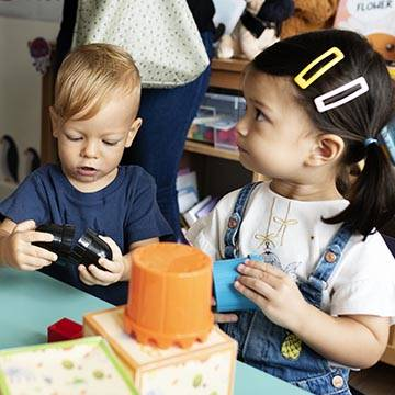 two toddlers playing with toys at table