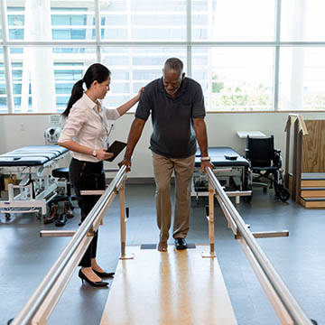 man assisted with physical therapy