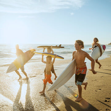 Family carrying surfboards at beach