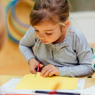 5-year-old girl cuts construction paper with scissors