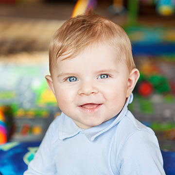 Baby boy smiling while seated at day care