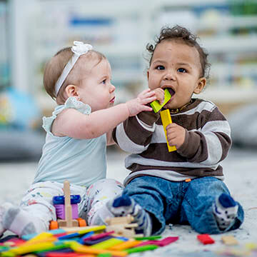Two babies seated playing with wooden blocks