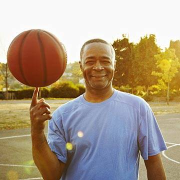 middle aged man spinning basketball on finger