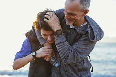 Father playful with teen son at beach