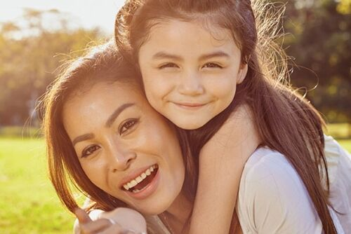 Mother smiling with young daughter on her back
