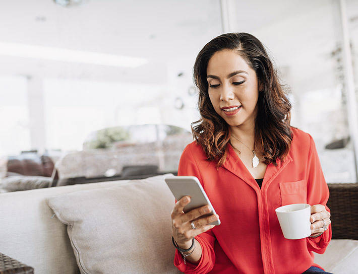 woman-looking-at-phone-drinking-coffee