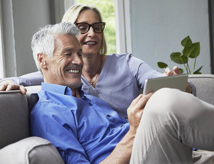 senior couple smiling while looking at tablet