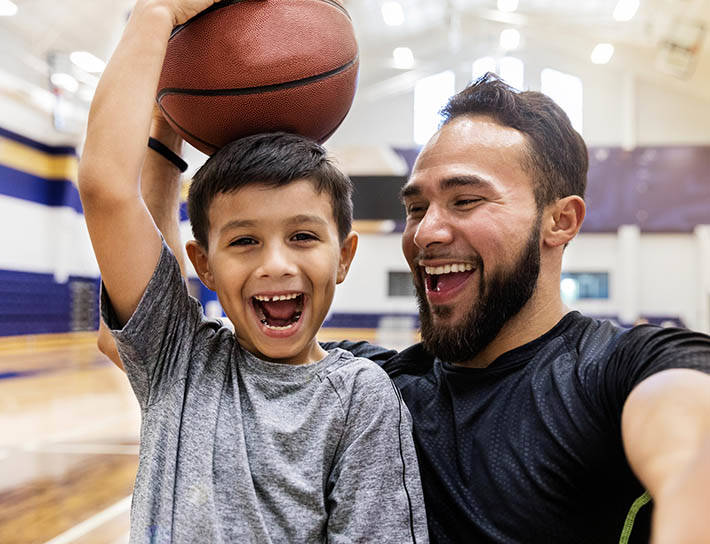father takes selfie with son holding basketball