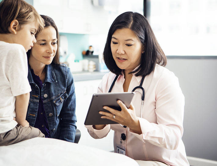Doctor showing mother and son results on tablet
