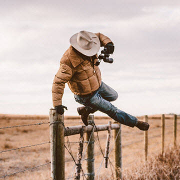 Rancher jumping over barbed wire fence.