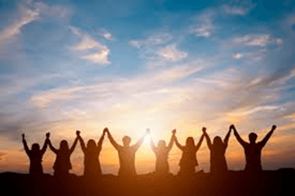 Group of people holding hands at sunrise