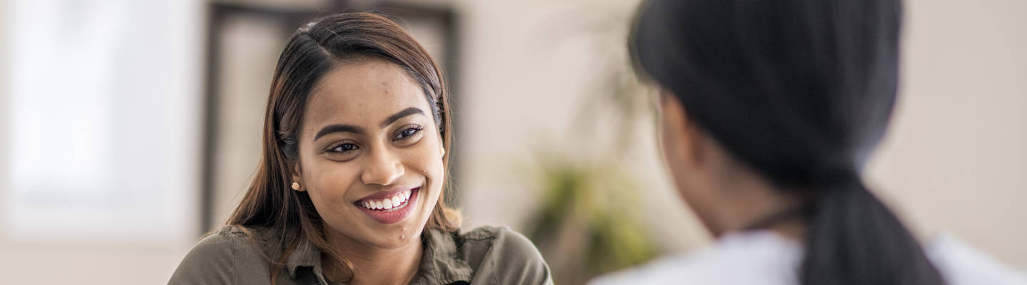 Woman smiles while speaking with counselor