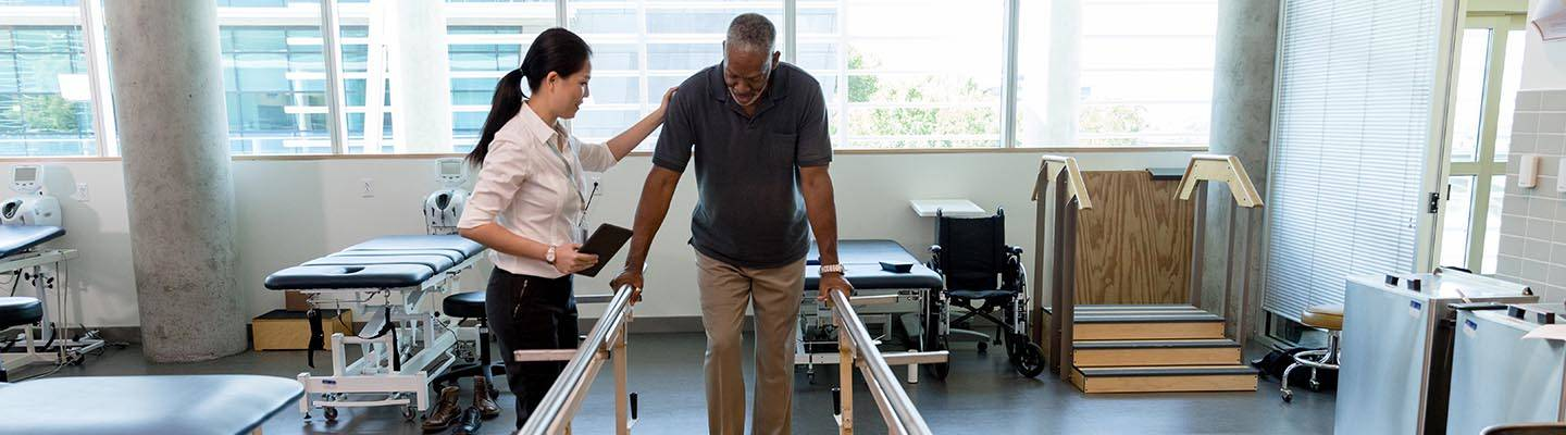 Man being assisted with physical therapy