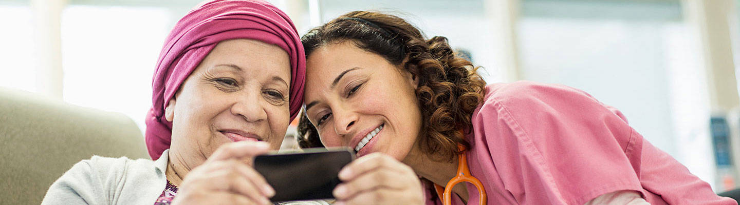 Cancer female with headband smiling at phone with a caregiver