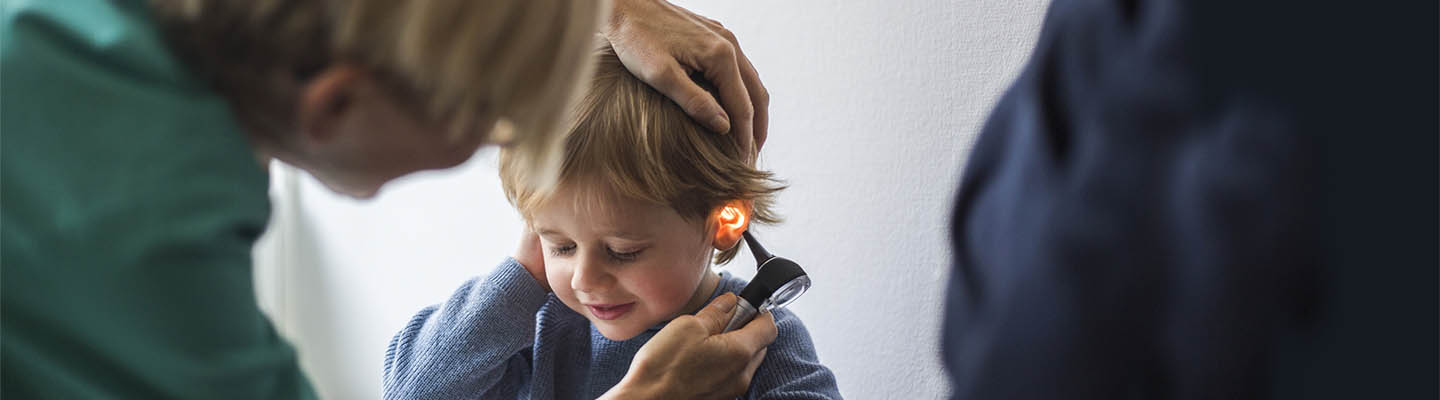 doctor uses otoscope on little boy
