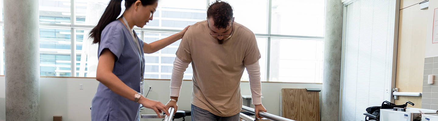 Physical therapy session with patient on parallel bars
