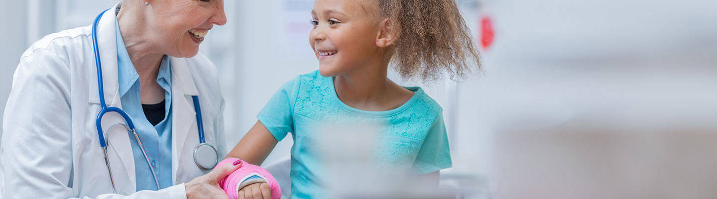 Little girl with arm cast smiling at her pediatrician