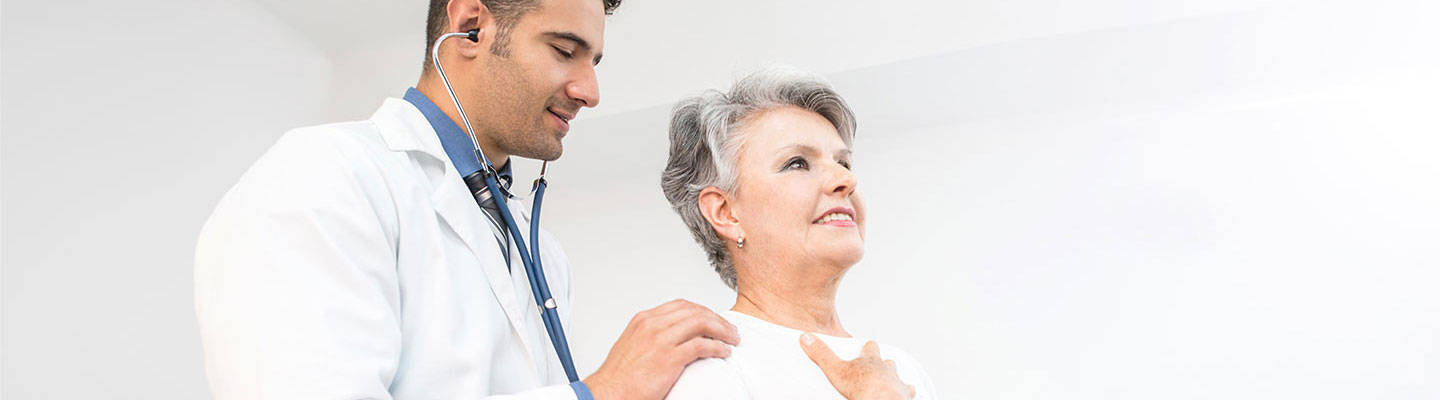 Male doctor examining senior woman with a stethoscope