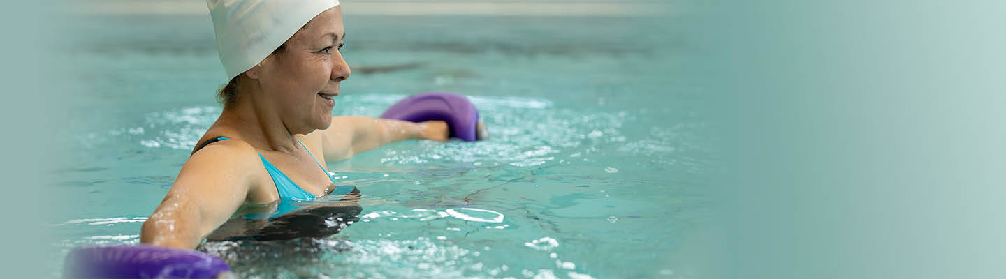 woman in pool holding weights