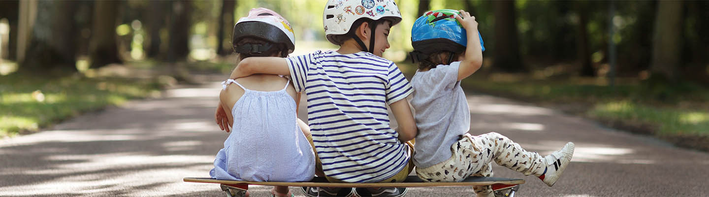 brother and two sisters sitting on skateboard