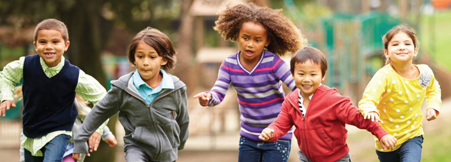 Diverse group of children running on playground