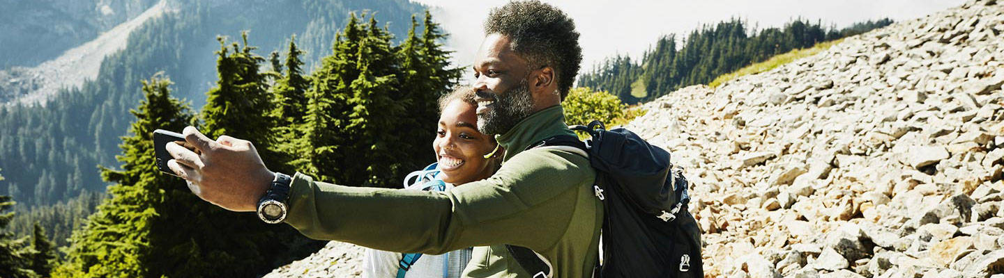 Father and daughter taking selfie while hiking