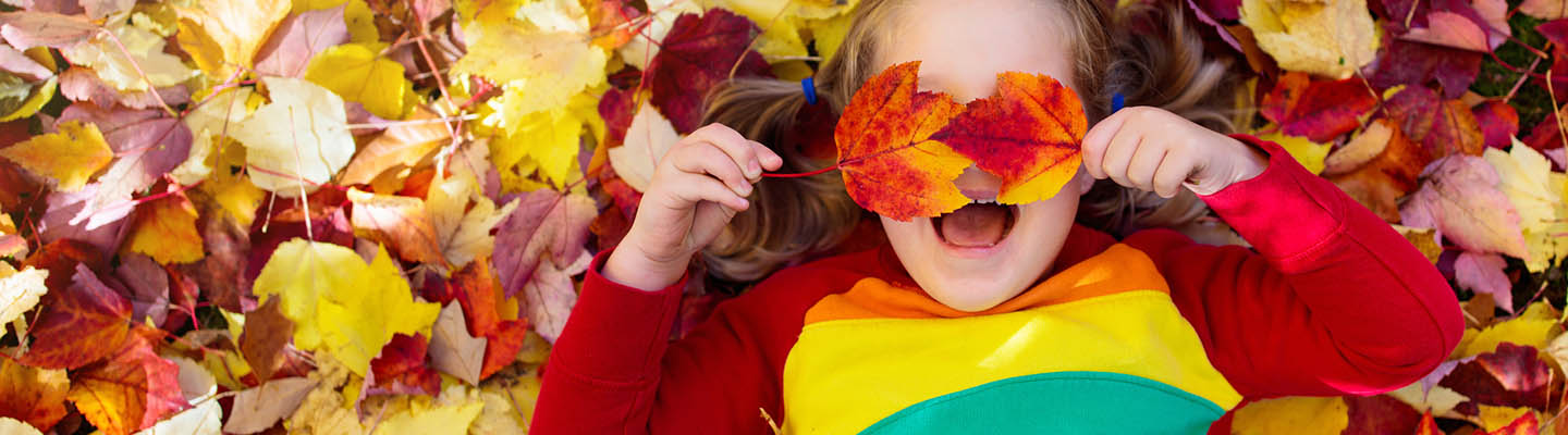 Girl covering eyes with fall leaves