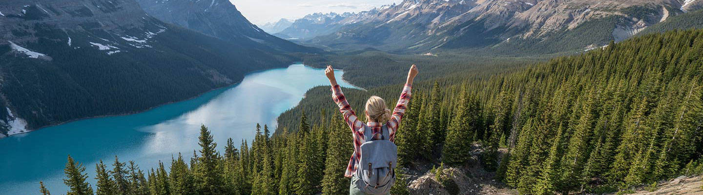 Girl lifting hands while hiking in the mountains
