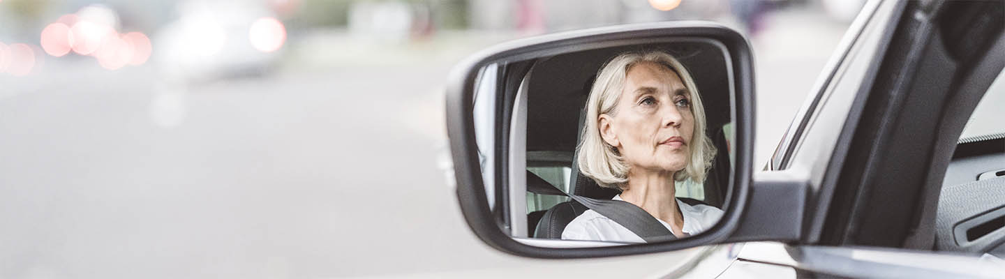 reflection of woman in car side view mirror