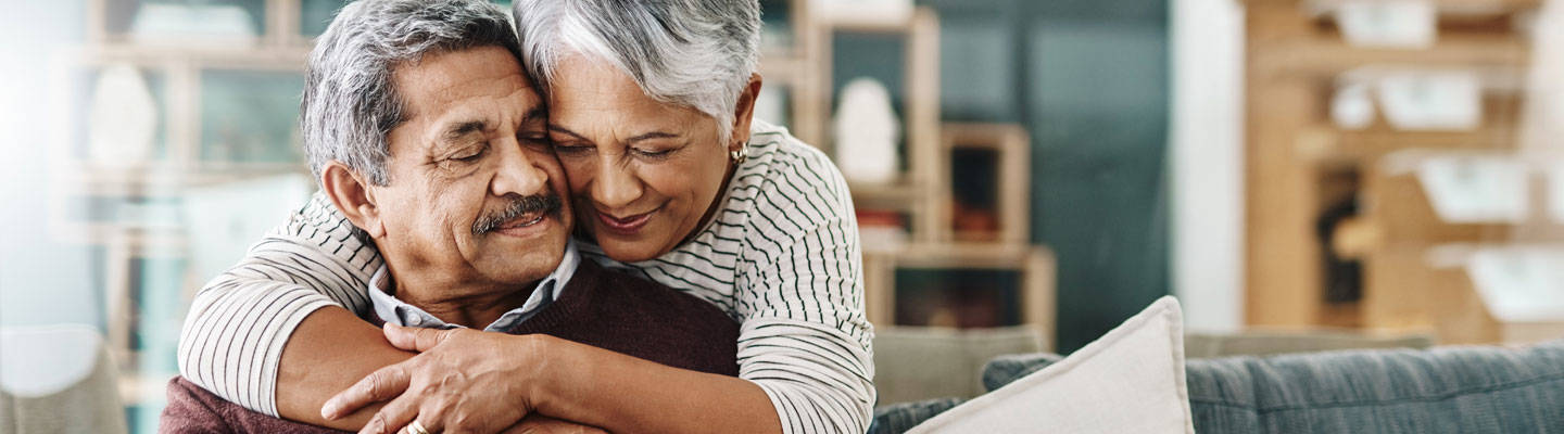 Senior woman hugging her husband sitting on couch