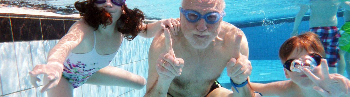 Grandfather swimming with 2 young kids