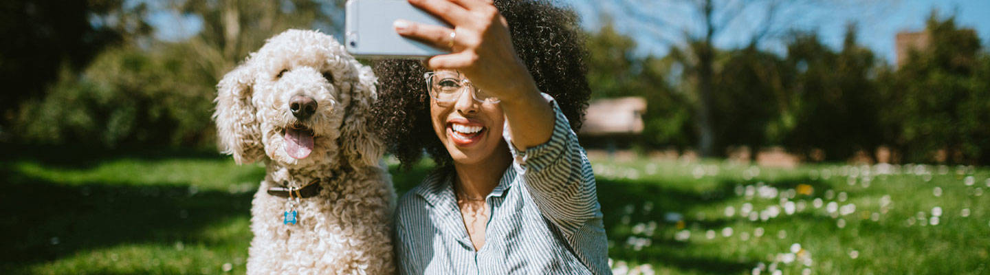 Woman taking selfie with cute dog at park