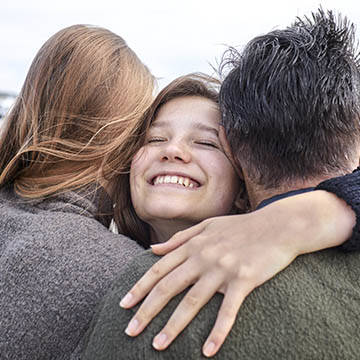 happy girl hugging mother and father