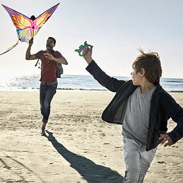 father and son fly kite on beach
