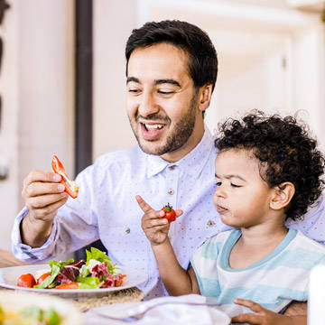 Father and young son eating salad
