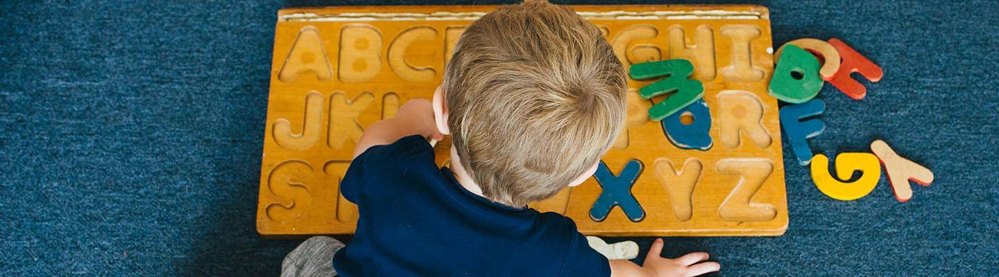 toddler playing with wooden alphabet
